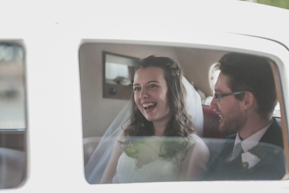 Bride and groom in the back of a wedding car