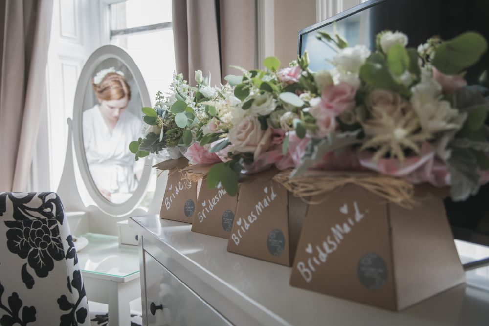 Bride and bridesmaid flowers in a row in front of a bride in a mirror